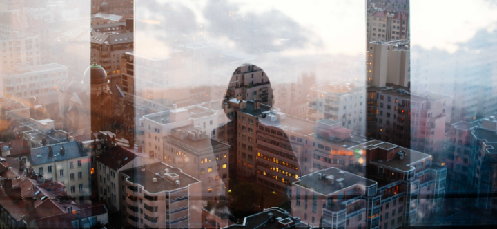 image of person looking out window at buildings