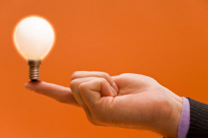 Image of a hand balancing a light bulb for innovation